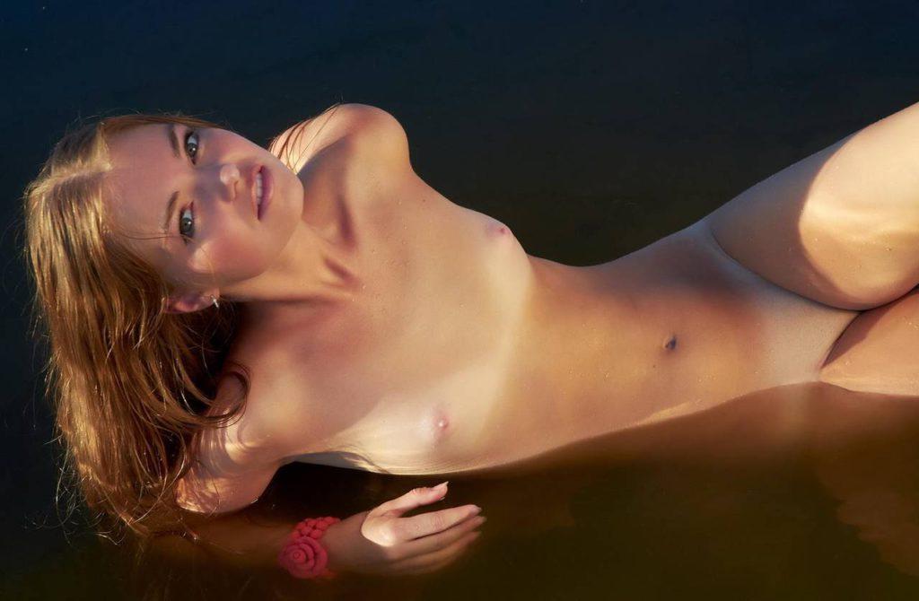 Голая шатенка позирует в воде
