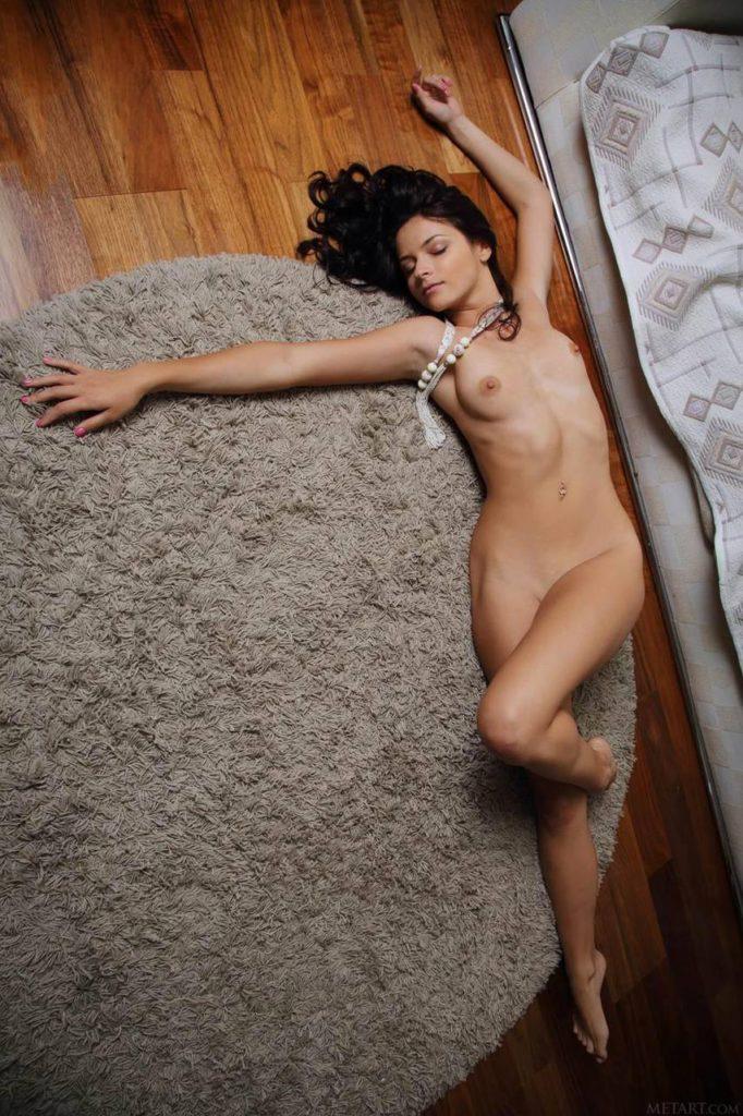 Красивая голая брюнетка на ковре