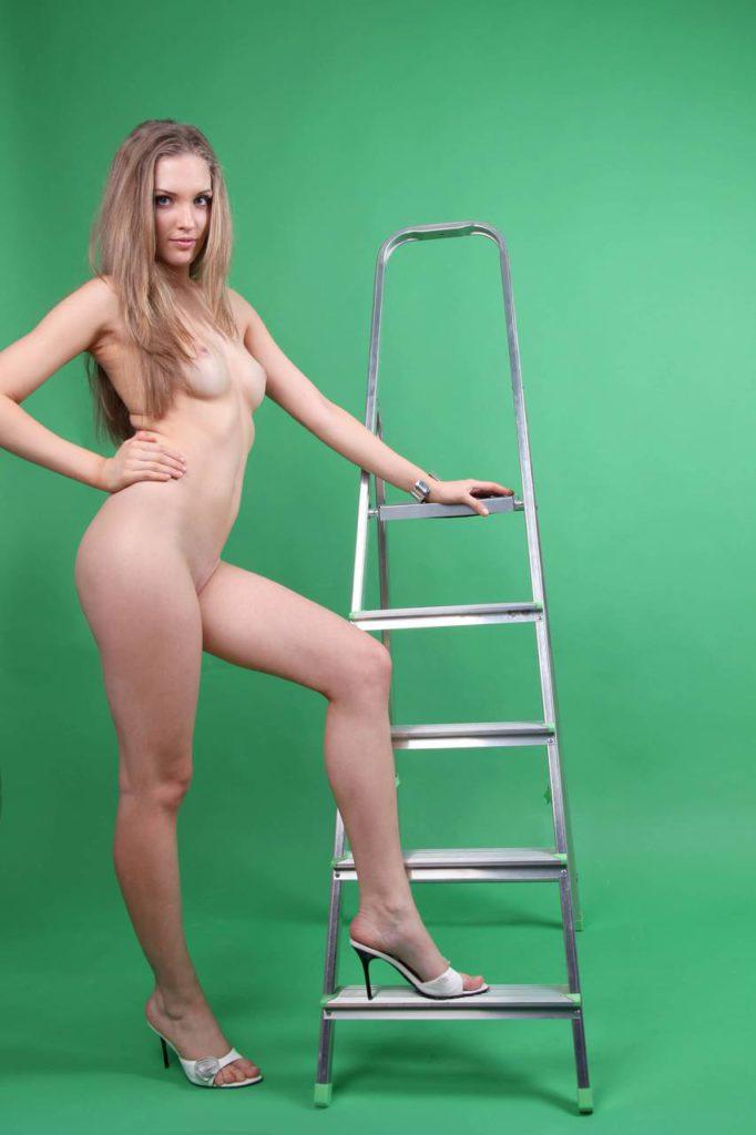 Красивая блондинка стоит голышом рядом с лестницей