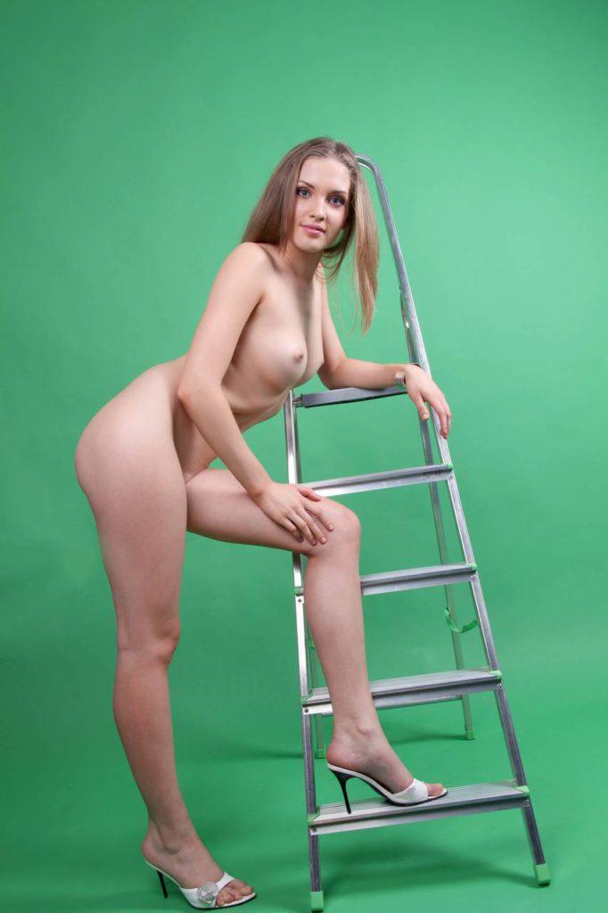 Молодая блондиночка стоит голышом у лестницы