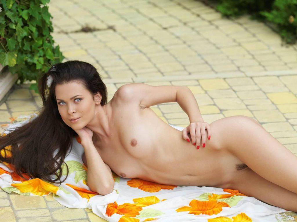 Молодая красавица показывает грудь лежа