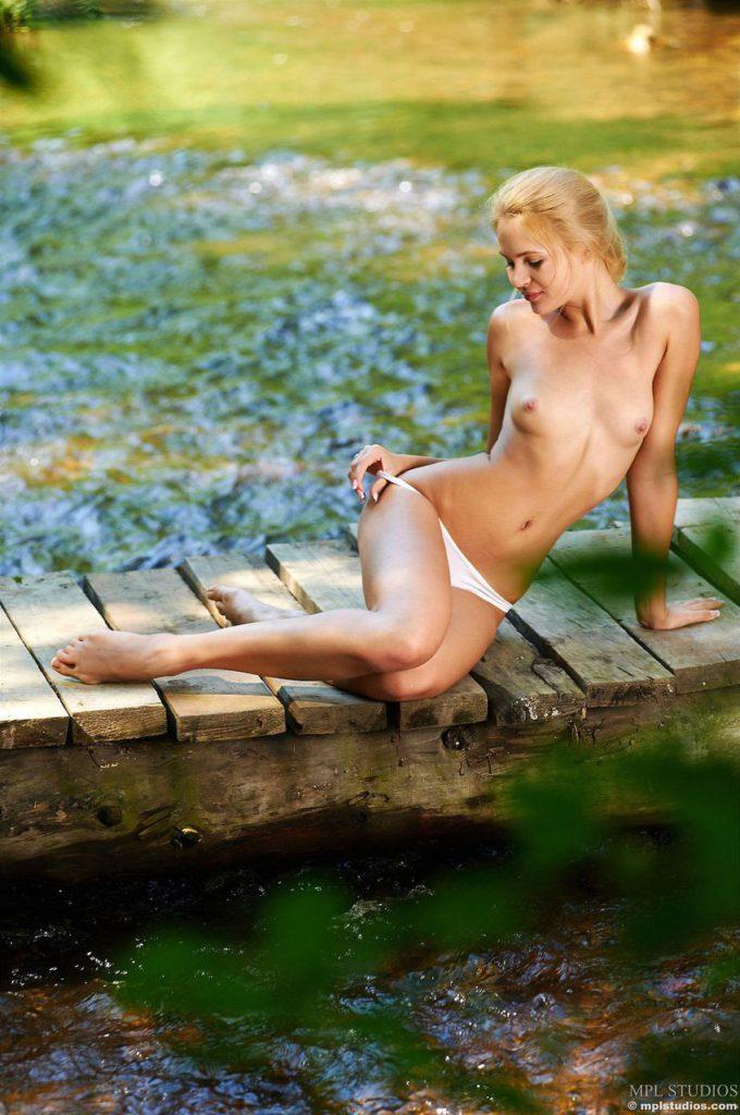 Девушка с голой грудью готовится снять трусы