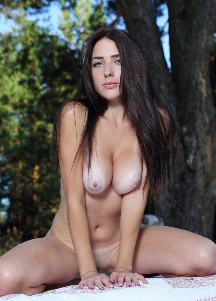 Красивая брюнетка сидит голышом в лесу