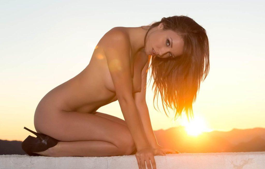 Голая молодая девушка сидит на закате