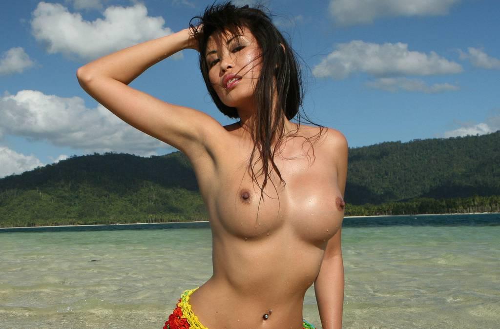 Красивая азиатка показывает голую грудь на пляже