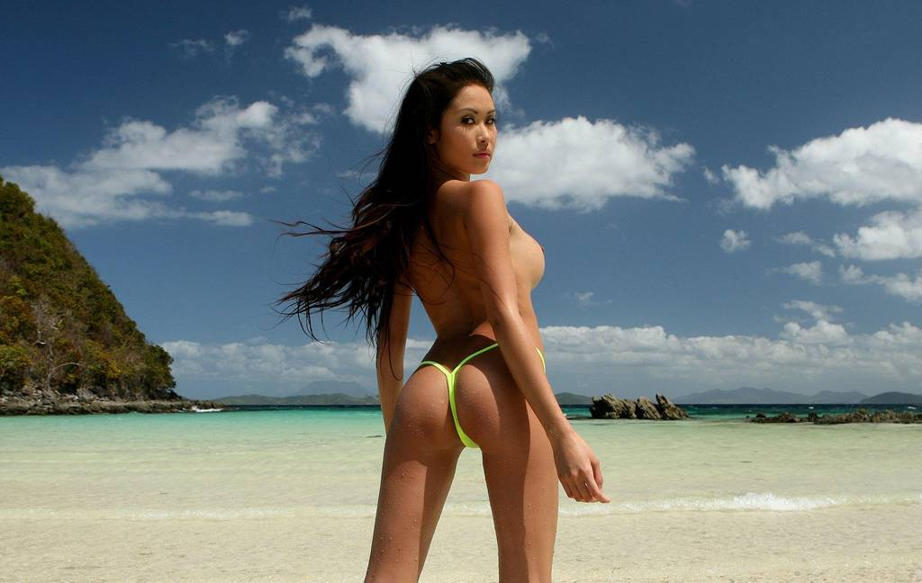 Азиатка с обнаженной грудью на фоне моря